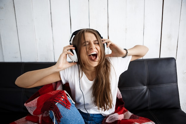 ソファーに座っていたヘッドフォンで音楽を聴く格子縞の女性。
