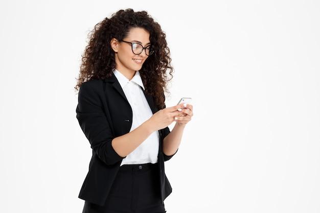 携帯電話を見て眼鏡をかけている陽気な巻き毛ビジネス少女