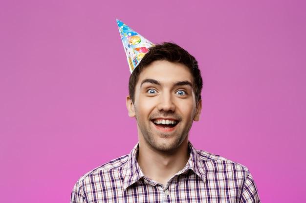 紫色の壁を越えて笑っている陽気な若いハンサムな男。誕生日会。