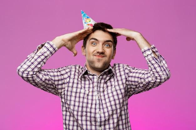 陽気なハンサムな男の笑みを浮かべて、紫色の壁に喜び。誕生日会。