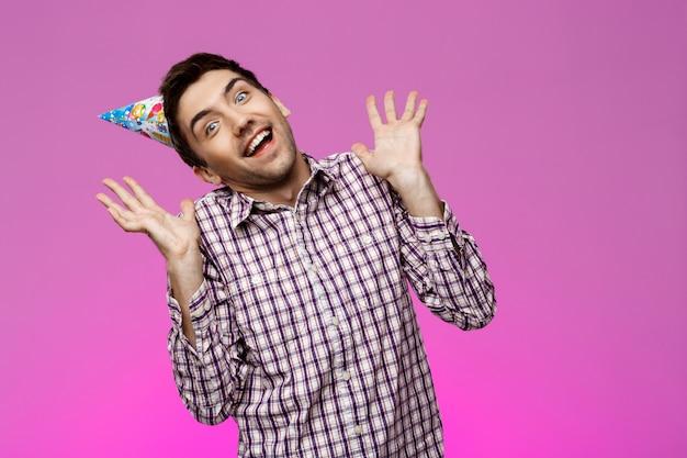 Веселый красавец улыбается, радуясь над фиолетовой стеной. день рождения.