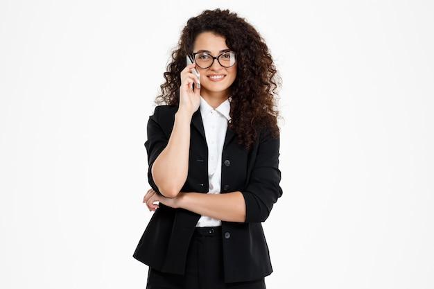 Веселая кудрявая деловая девушка в очках разговаривает по телефону