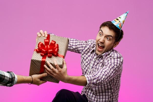 紫色の壁の上のボックスで誕生日プレゼントを引き裂く男。
