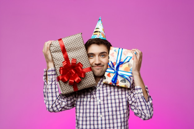 紫色の壁の上のボックスに誕生日プレゼントを置く幸せな男。