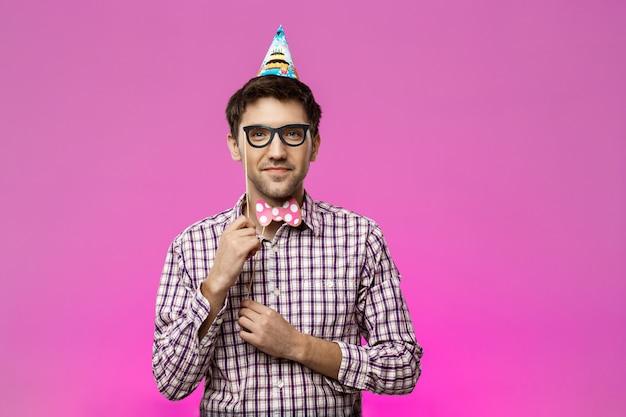 偽の眼鏡と紫の壁に蝶を身に着けている若い男。