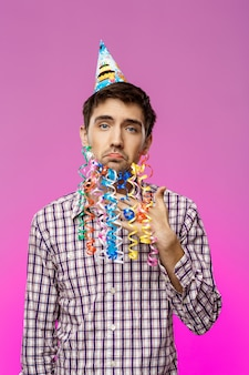 偽のひげの誕生日パーティーでポーズを持つ若いハンサムな男。