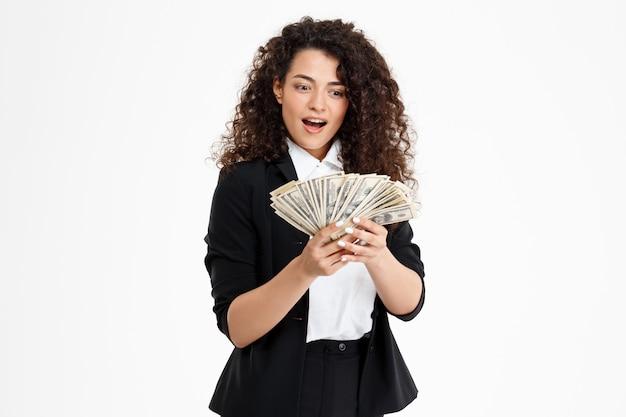 Веселый кудрявый бизнес девушка держит деньги