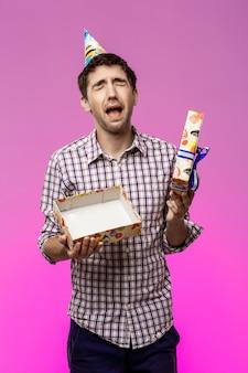 悲しい若いハンサムな男が紫色の壁に誕生日プレゼントを開きます。