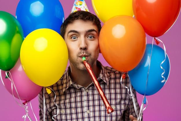 Молодой человек празднует день рождения, держа красочные шарики над фиолетовой стеной.