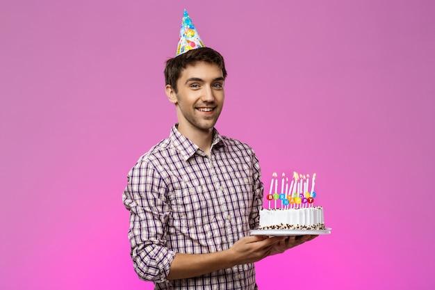 笑みを浮かべて、紫色の壁に誕生日ケーキを置く若いハンサムな男。