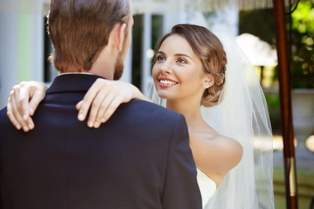 幸せな美しい新婚夫婦の笑顔、抱きしめ、お互いを見て。