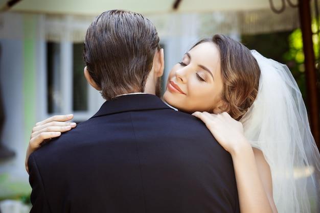 Счастливые красивые молодожены улыбаясь, обнимая в кафе на открытом воздухе. глаза закрыты.