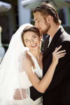 幸せな美しい新婚夫婦が笑みを浮かべて、抱きしめ、外でキスします。