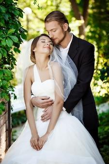 公園で抱きしめる目を閉じて笑って幸せな新婚夫婦。