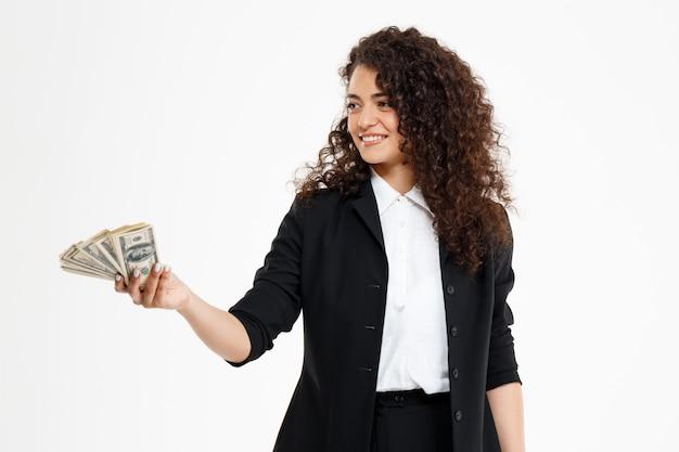 お金を保持している陽気な巻き毛ビジネス少女