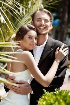 Молодая красивая пара молодоженов улыбаясь, обнимая в парке.
