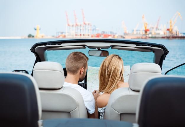 車に座って、地図を見て若い美しいカップル。