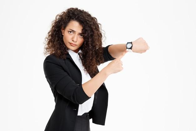 Молодая нежная кудрявая девушка смотрит на часы и переживает, что поздно
