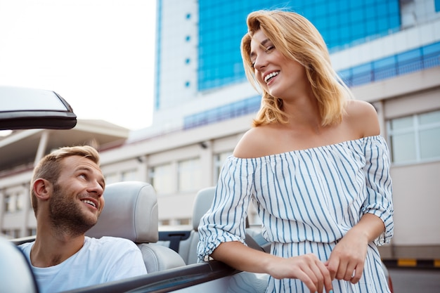 笑みを浮かべて、海の近くの車に座っている若い美しいカップル。