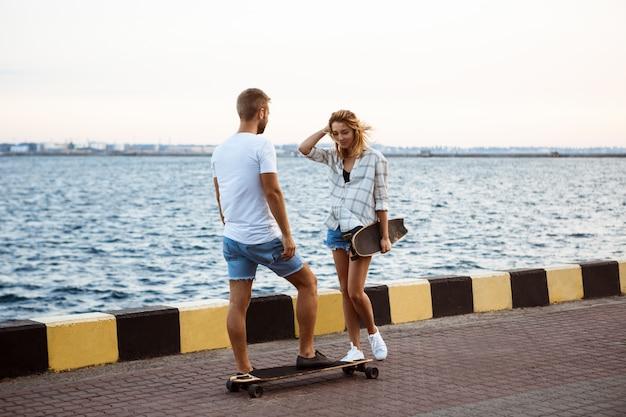 Молодая красивая пара прогулки на море, улыбаясь, скейтбординг.