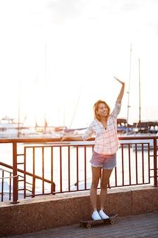 Молодая красивая женщина, прогулки на берегу моря, улыбаясь, приветствие, скейтбординг.