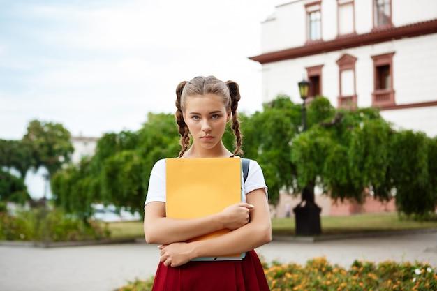 屋外でフォルダーを探して保持している動揺の若い美しい女子学生
