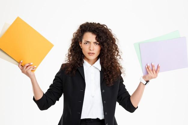 Молодая смущенная курчавая девушка держа документы