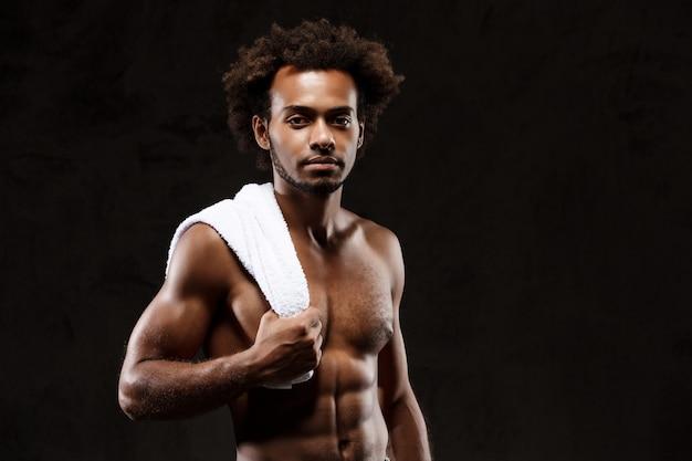 Молодой спортивный африканский человек представляя над черной стеной.