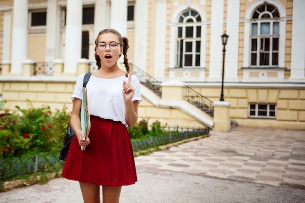 Молодая красивая студентка в очках, держа папки, думая на открытом воздухе.