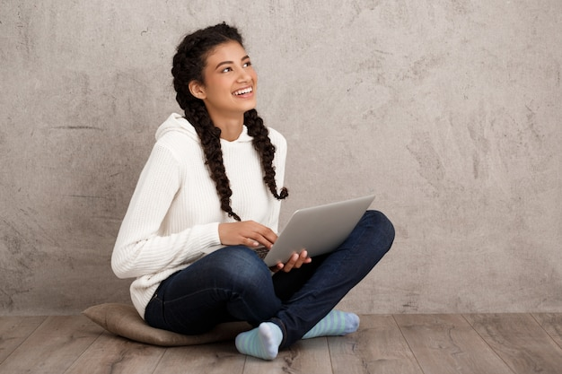 Девушка улыбается, держа ноутбук, сидя на полу над бежевой стеной