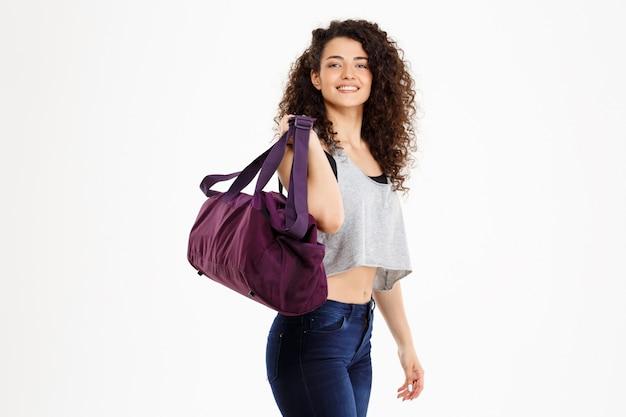 Фитнес кудрявая девушка держит спортивную сумку
