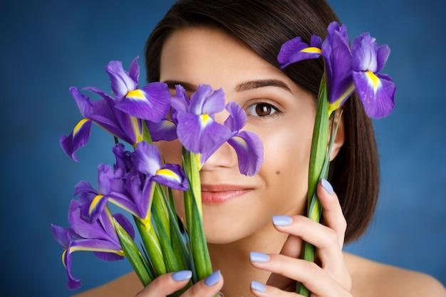 Крупным планом портрет нежной молодой женщины за фиолетовыми цветами над синей стеной