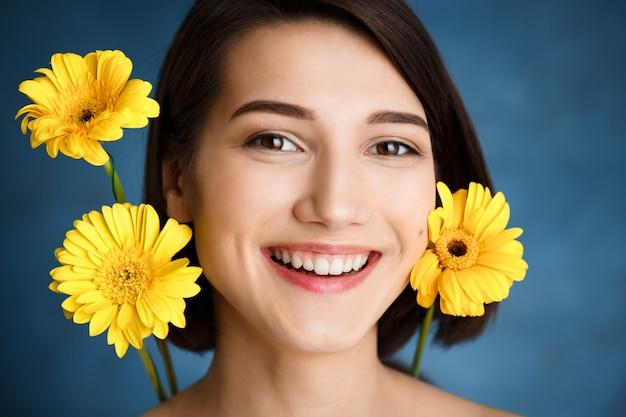 Крупным планом портрет нежной молодой женщины с желтыми цветами над синей стеной