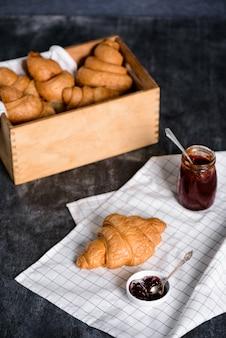 Круассаны в деревянной коробке и горшок с джемом в сторону на сером столе