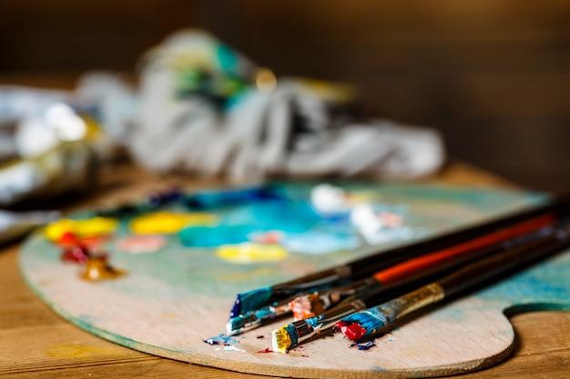 油絵の具とパレットのブラシのクローズアップ