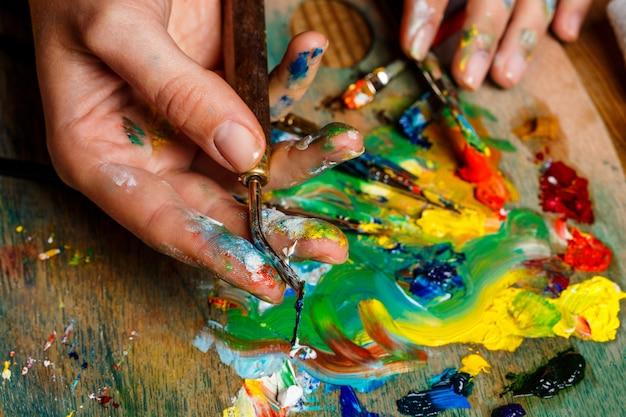 パレットに油絵の具を混合する女性の写真をクローズアップ