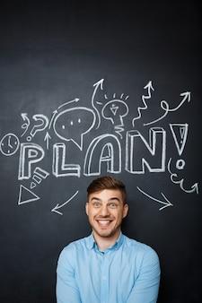 計画概念と黒板の上に立っている人