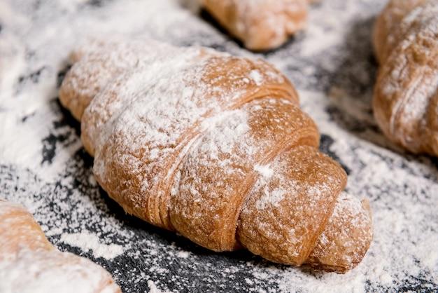 灰色のテーブルに粉砂糖をクロワッサン。