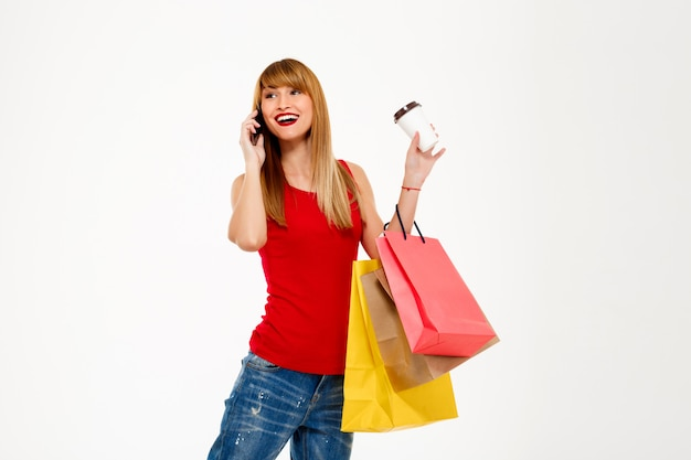 白い壁を越えて購入で立っている若い美しい女性