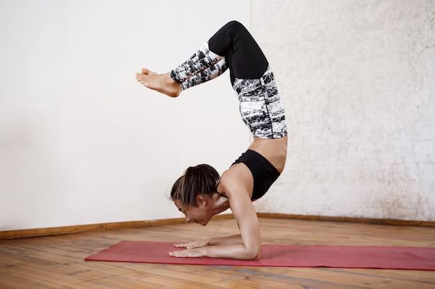 赤いマットで屋内ヨガを練習して若い運動美人