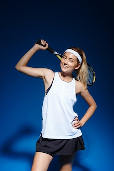 Теннисистка с ракеткой на плече позирует