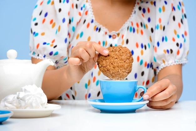 Крупным планом женских рук, окуная печенье в молоке