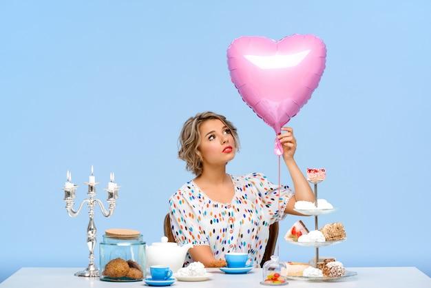青い壁の上にお菓子を持つ若い美しい女性の肖像画