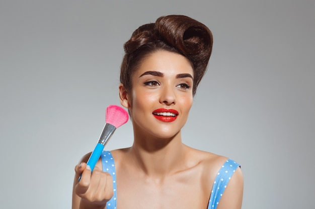 メイクアップブラシを保持している美しいピンナップ女性の肖像画