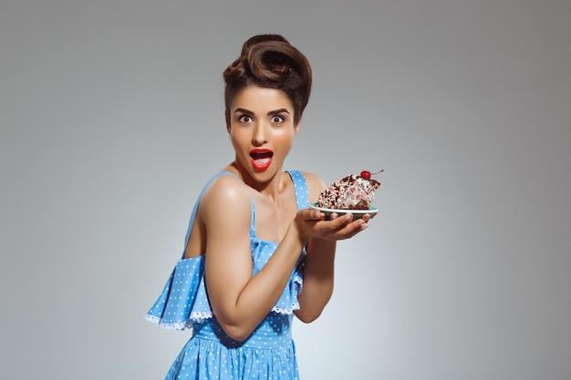 手でケーキを保持している美しいピンナップ女性の肖像画