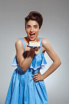 手でケーキを保持している美しい面白いピンナップ女性の肖像画