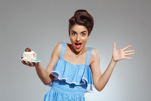 手でケーキを保持している美しい幸せなピンナップ女性の肖像画