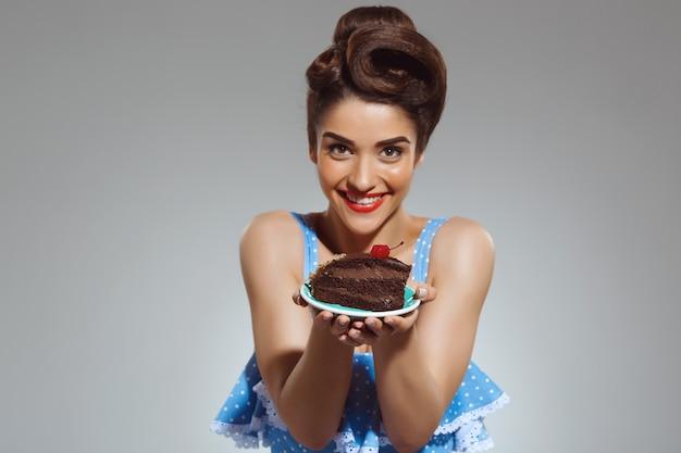 Портрет красивой очаровательной женщины, держащей торт в руках