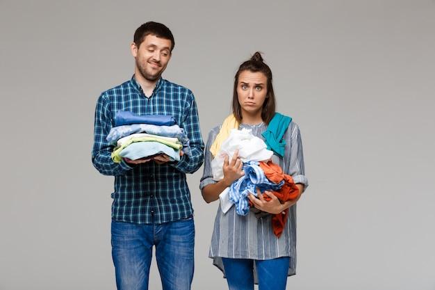 Молодая красивая пара держит стирку одежды над серой стеной