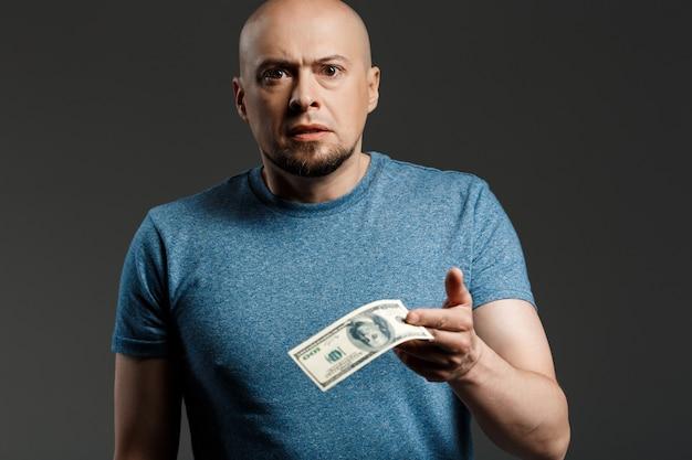 暗い壁を越えてお金を保持している灰色のシャツでハンサムな男の肖像